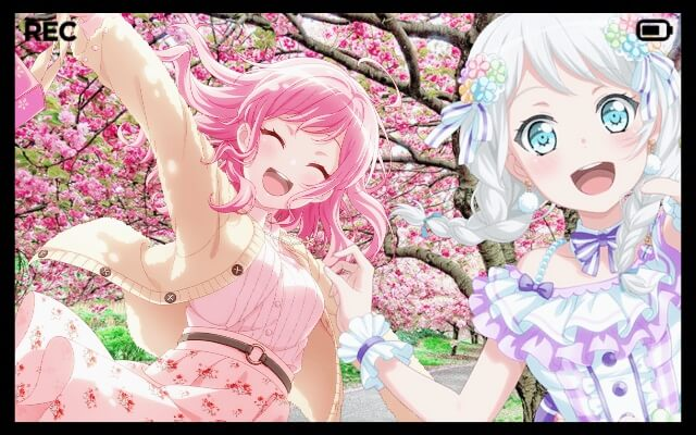 Eve and Aya take a video while walking down a cherry blossom path.